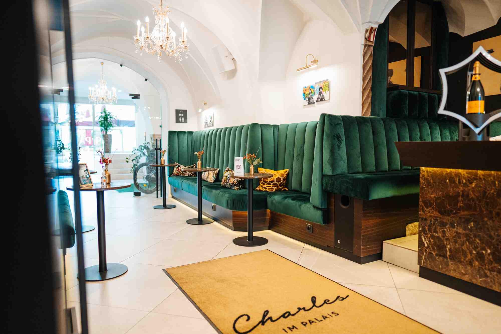 gruener samt sitzbereich im flur im hotel palais26 villach
